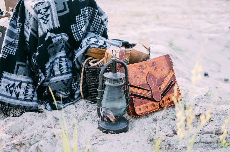 Vecchia lampada di cherosene vicino alla borsa d'annata di boho, canestro con legna da ardere e coperta di hippy immagine stock