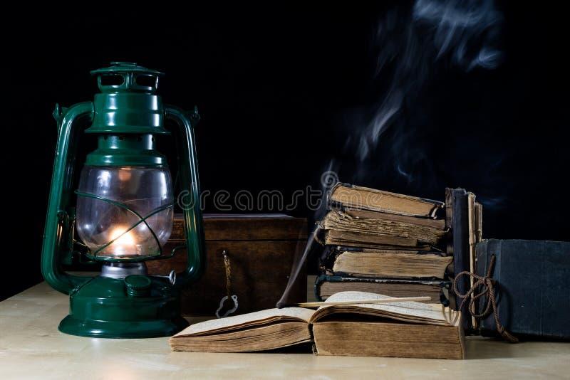 Vecchia lampada a olio e libri che si trovano sulla tavola Una fiamma da una vecchia s fotografia stock