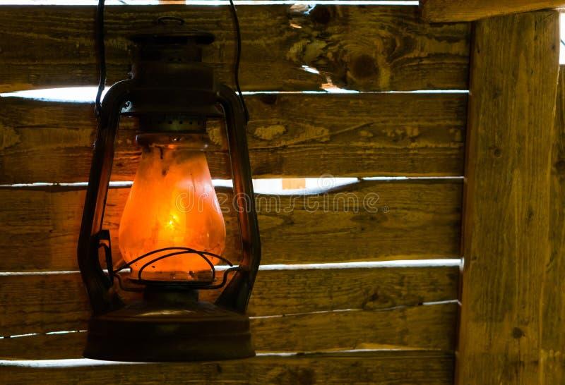 Vecchia lanterna accesa dei minatori che appende su alcune plance di legno, decorazioni d'annata immagini stock
