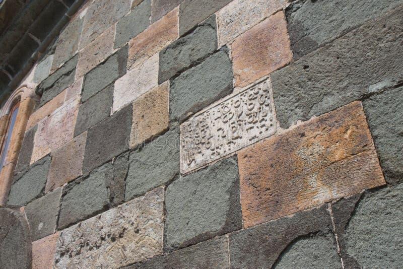 Vecchia lapide su un antico tempio Frammento di vecchia iscrizione sulla pietra in georgiano fotografia stock libera da diritti