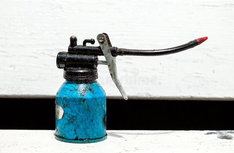 Vecchia latta dell'olio, pompa di olio tenuta in mano vecchia immagine stock