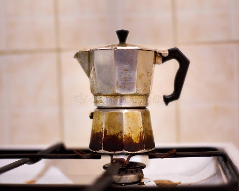 Vecchia latta di caffè frequentemente utilizzata d'annata di Moka sul fornello di gas fotografia stock libera da diritti