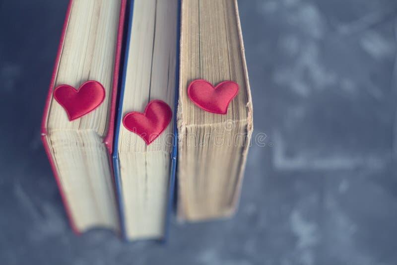 Vecchia libreria i precedenti blu con la vista superiore dei piccoli cuori rossi Libri di lettura di amore fotografie stock