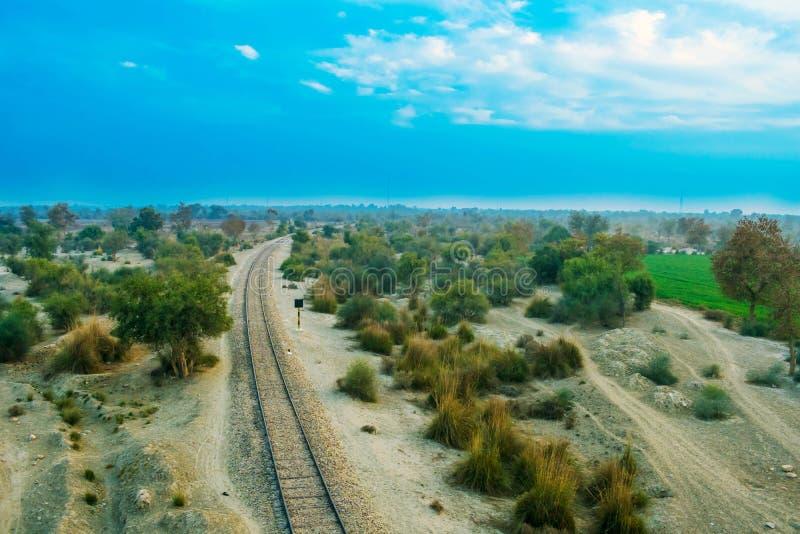 Vecchia linea ferroviaria in una foresta con il cielo nuvoloso fotografia stock libera da diritti