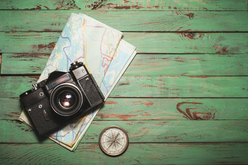 Vecchia macchina fotografica d'annata della foto con la bussola e mappa su fondo di legno immagini stock libere da diritti