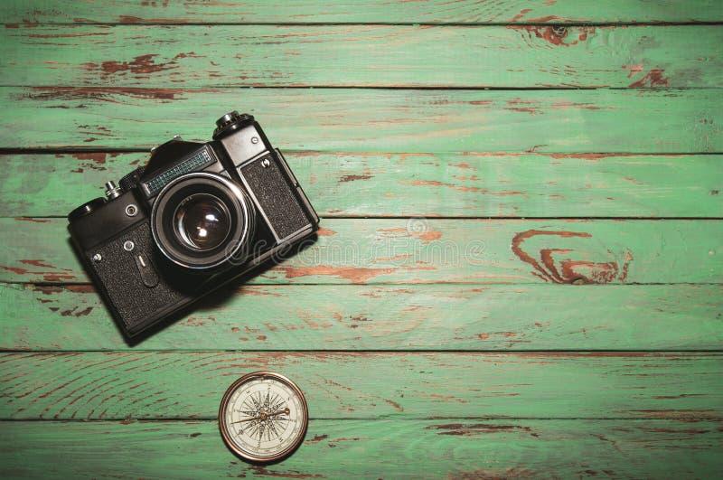 Vecchia macchina fotografica d'annata della foto con la bussola su fondo di legno fotografie stock libere da diritti