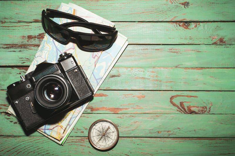Vecchia macchina fotografica d'annata della foto con la mappa, la bussola ed i vetri scuri su fondo di legno immagini stock