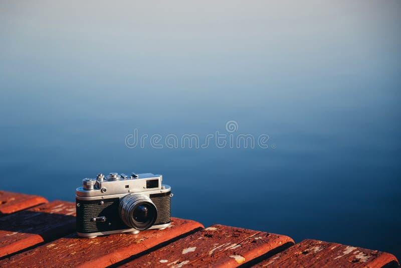 Vecchia macchina fotografica d'annata della foto del film che si trova sull'ancoraggio di legno, fondo blu scuro dell'acqua Copi  fotografie stock libere da diritti