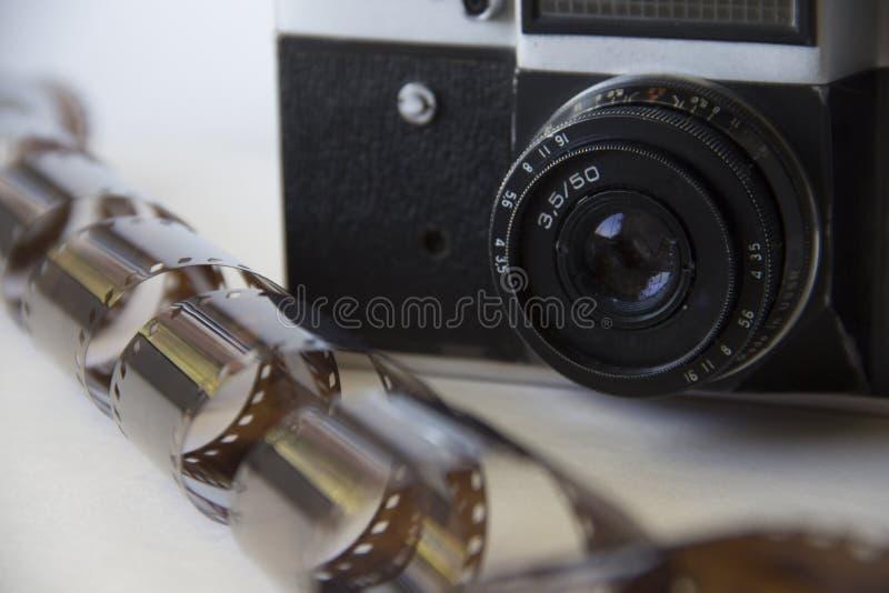 Vecchia macchina fotografica su fondo bianco con il film immagini stock