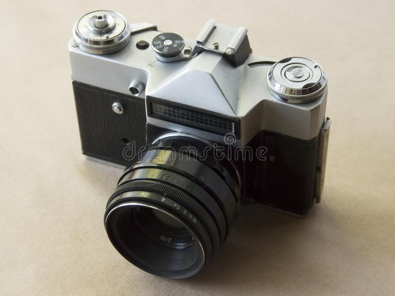 Vecchia macchina fotografica sui precedenti della carta kraft con il film fotografie stock