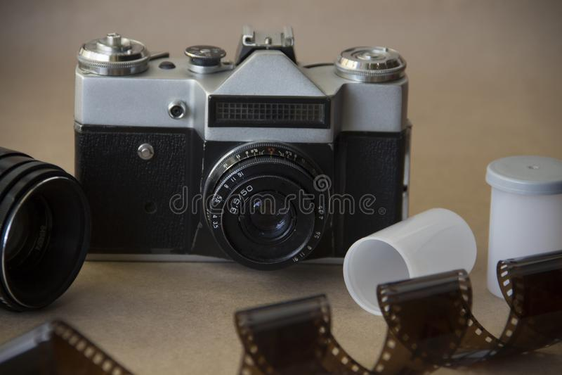 Vecchia macchina fotografica sul fondo della carta kraft con il film e le foto stampate fotografia stock libera da diritti