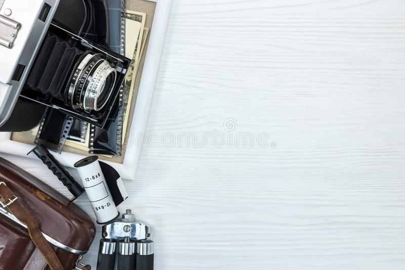 Vecchia macchina fotografica, treppiede, struttura della foto e vecchie immagini su backgr bianco immagine stock