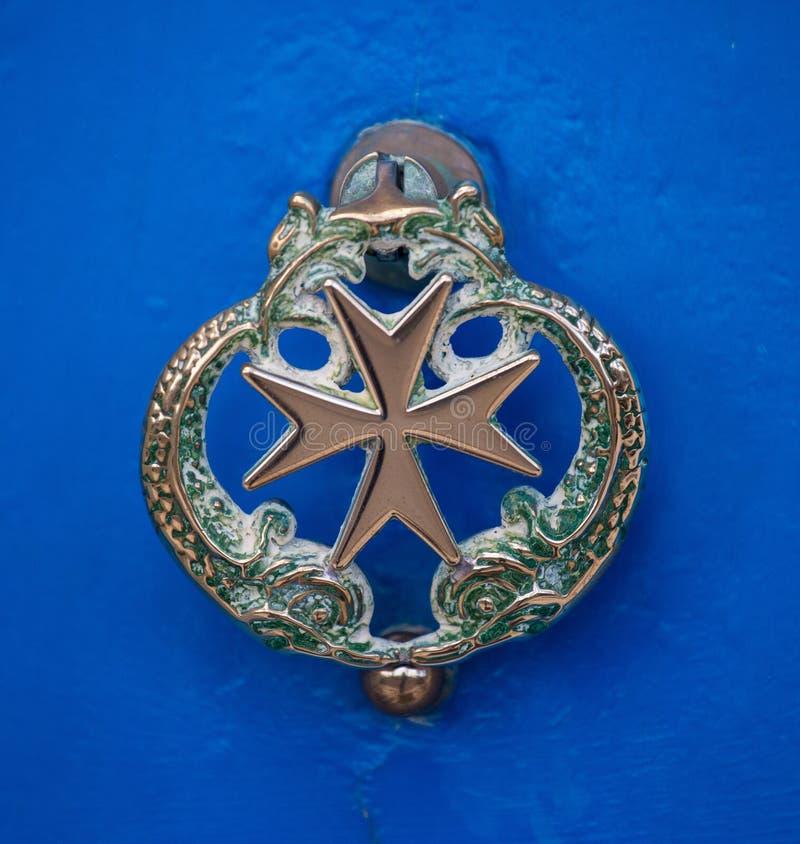 Vecchia maniglia del delfino della porta con la croce di Malta sulla porta azzurrata, La Valletta, Malta immagini stock libere da diritti