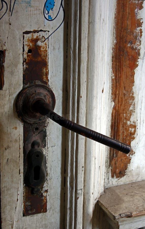 Vecchia, maniglia di porta arrugginita d'annata su una porta bianca invecchiata fotografia stock libera da diritti