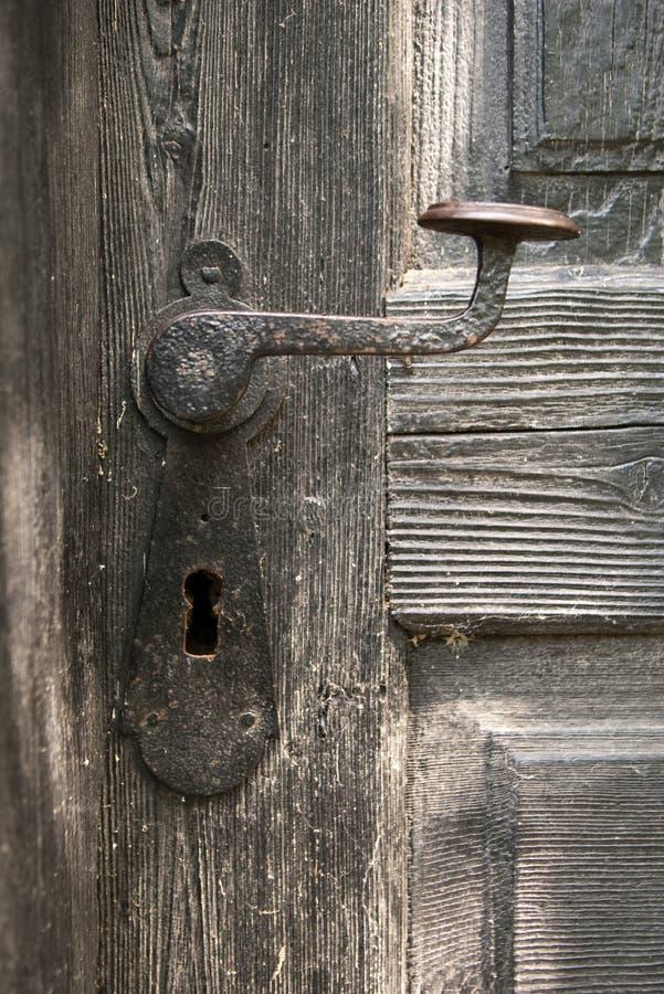 Vecchia maniglia di portello sul portello di legno fotografia stock