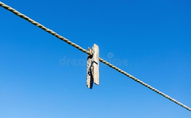 Vecchia molletta da bucato di legno sulla corda contro il cielo immagini stock