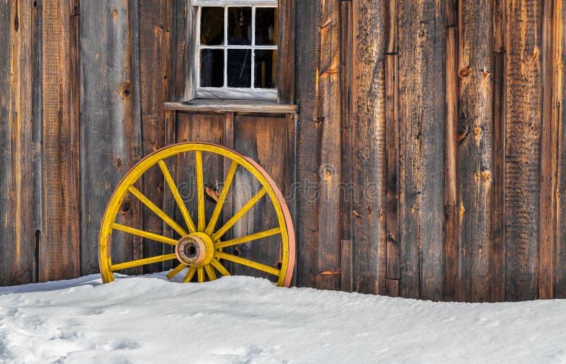 Vecchia neve gialla di legno antica della ruota di vagone fotografia stock libera da diritti