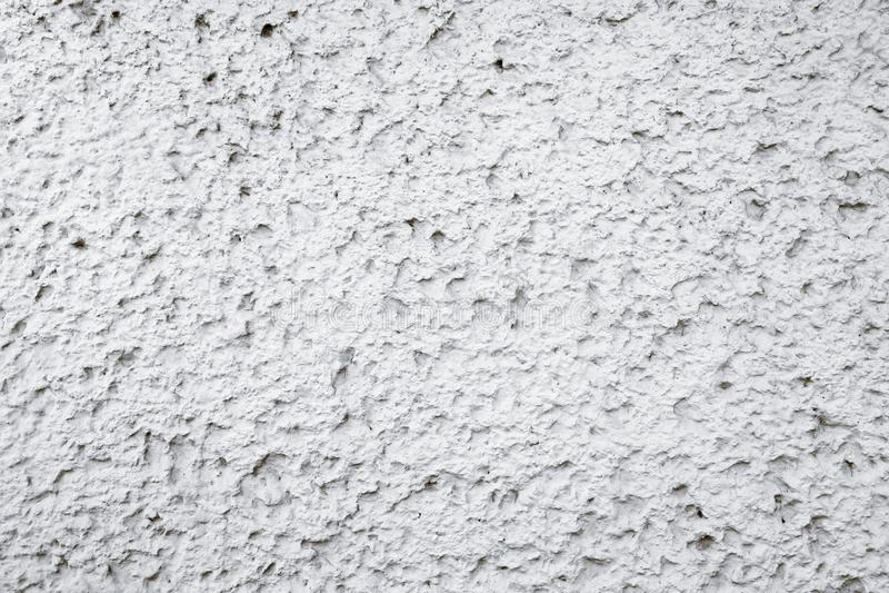 Vecchia parete concreta bianca e grigia grungy del cemento con le imperfezioni come fondo di struttura di superficie ruvida fotografie stock