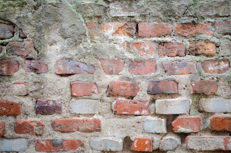 Vecchia parete concreta grigia del garage con i mattoni rossi ed il fondo delle crepe fotografia stock libera da diritti