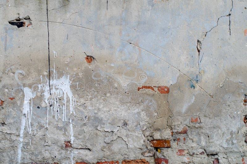 Vecchia parete concreta grigia del garage con le crepe ed i punti dei mattoni rossi fotografie stock libere da diritti