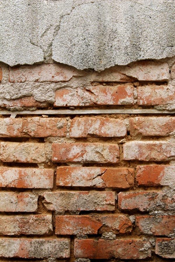 Vecchia parete dei mattoni rossi e del gesso rotto nocivo, fondo astratto Costruzione del muro di mattoni immagine stock libera da diritti