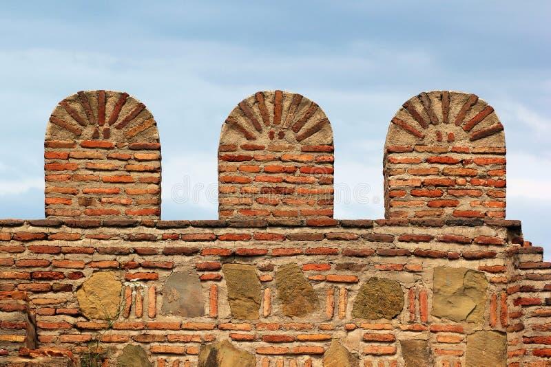 Vecchia parete della fortezza della pietra del mattone con i merli immagini stock libere da diritti