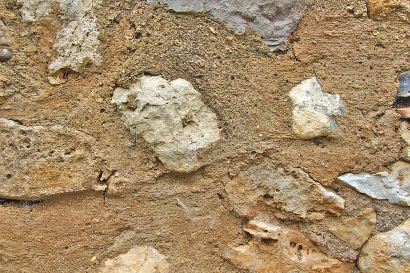 Vecchia parete di pietra grigia e marrone in una città fotografia stock