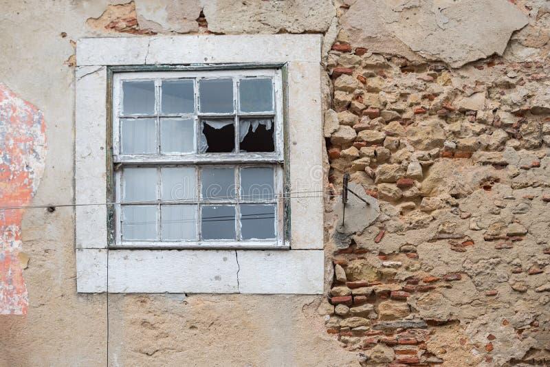 Vecchia parete friabile con gesso e finestra rotta, casa abbandonata immagini stock
