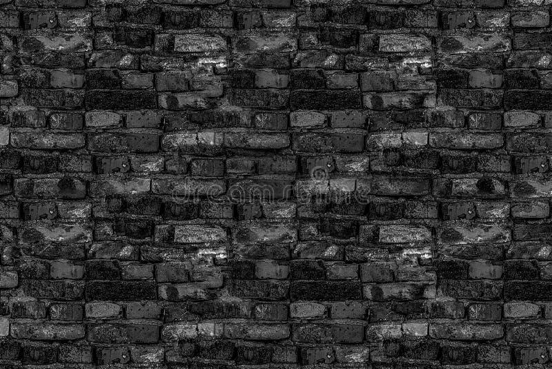 Vecchia parte nera rotta della parete di pietra della costruzione di casa rovinata nei mattoni rotti di toni tristi immagine stock