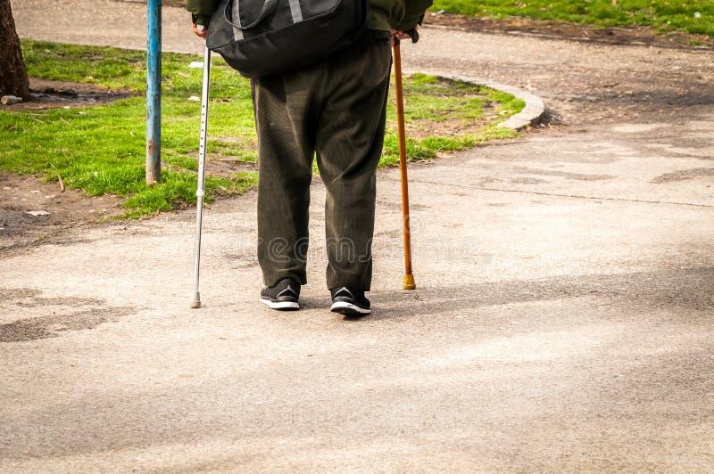Vecchia passeggiata depressa dell'uomo da solo giù la via con la vista sola e persa di sensibilità della canna o del bastone da p immagini stock
