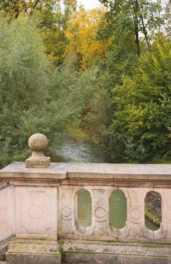 Vecchia passerella di pietra sopra insenatura nella caduta con i colori di autunno fotografia stock