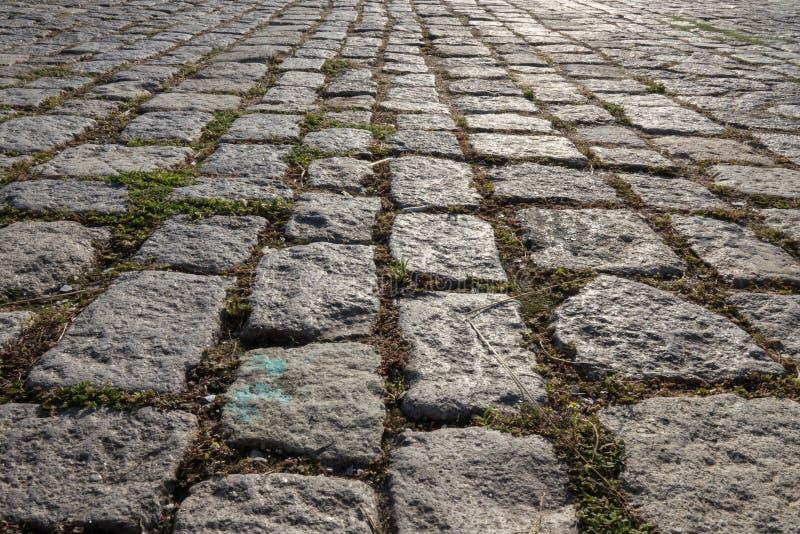 Vecchia pavimentazione del cobblestone Via con la pavimentazione cobblestoned del granito immagine stock libera da diritti
