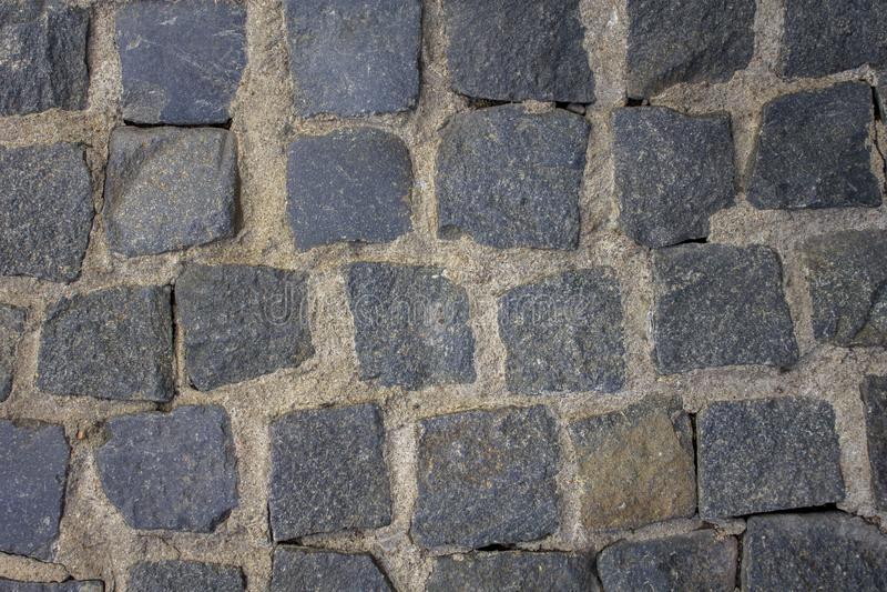 Vecchia pavimentazione di pietra delle pietre blu di varie forme e dimensioni con cemento leggero Struttura della superficie ruvi fotografia stock libera da diritti
