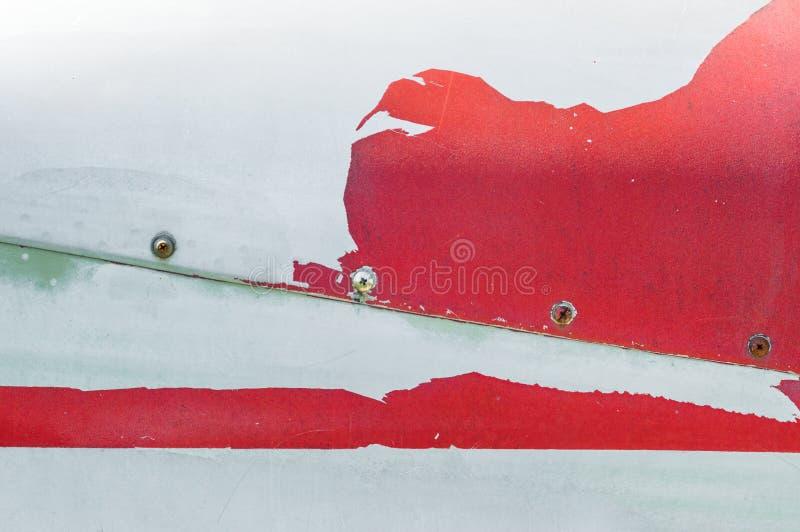 Vecchia pittura rossa di pelatura sulla superficie di metallo della fusoliera del airplace fotografie stock libere da diritti