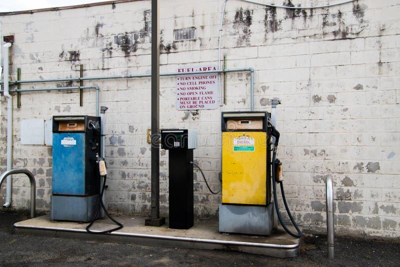 Vecchia pompa diesel gialla e vecchia pompa di benzina blu davanti al vecchio muro di mattoni bianco immagine stock