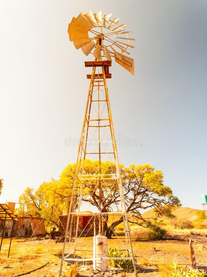 Vecchia pompa idraulica del mulino a vento nel paesaggio asciutto Costruzione metallica della torre fotografie stock libere da diritti