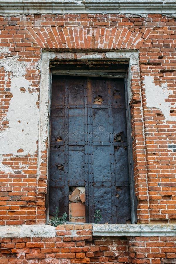 Vecchia porta arrugginita del metallo nella costruzione di mattone rosso antica rotta fotografia stock libera da diritti