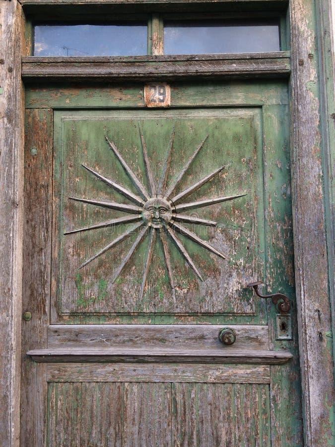 Vecchia porta con l'ornamento del sole e vecchia maniglia del ferro battuto fotografia stock libera da diritti