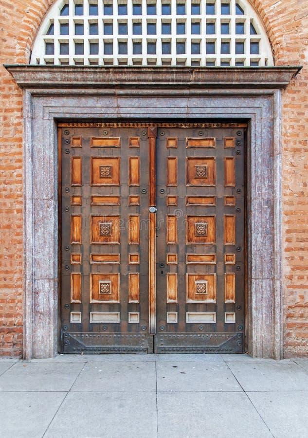 Vecchia porta d'annata della chiesa con il muro di mattoni rosso immagini stock libere da diritti