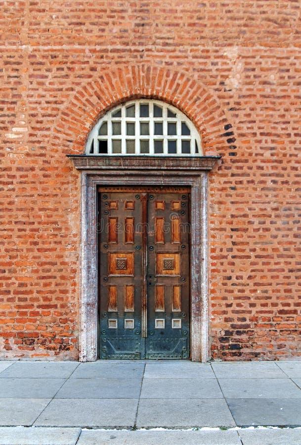 Vecchia porta d'annata della chiesa con il muro di mattoni rosso fotografie stock