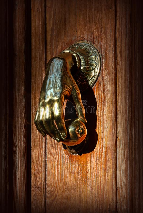 Vecchia porta di entrata con una maniglia sotto forma di una mano umana fotografia stock