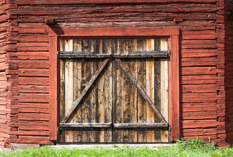 Vecchia porta di granaio stagionata su un granaio storico dipinto con la pittura famosa di rosso di Falu immagine stock