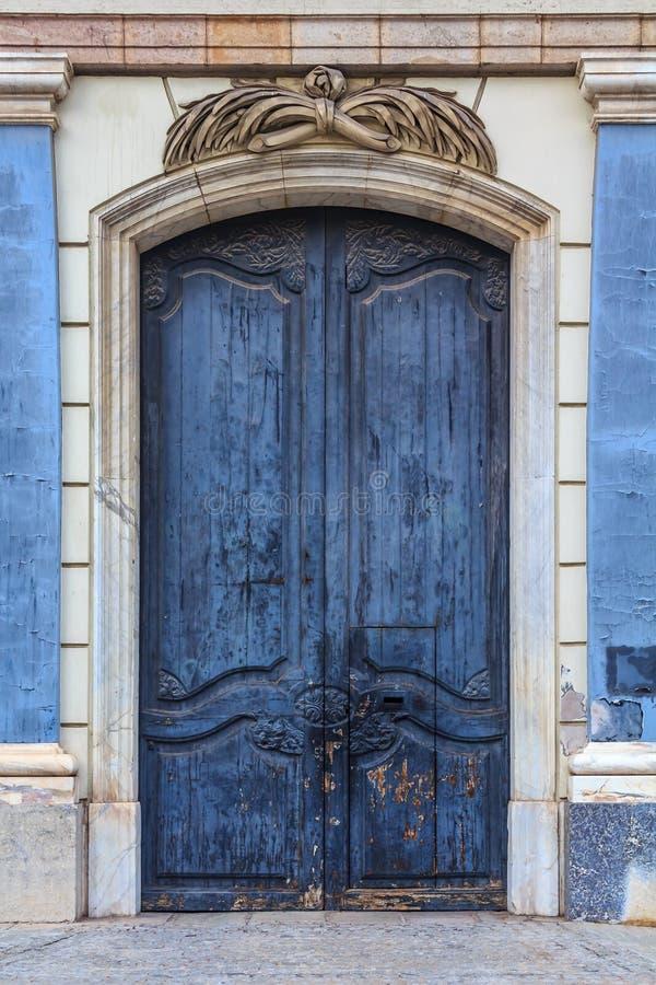 Vecchia porta di legno con la pelatura pittura e delle sculture blu nel Goth fotografie stock