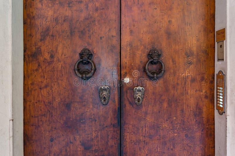 Vecchia porta di legno con le maniglie di porta ed i battitori complessi del dorr immagine stock libera da diritti
