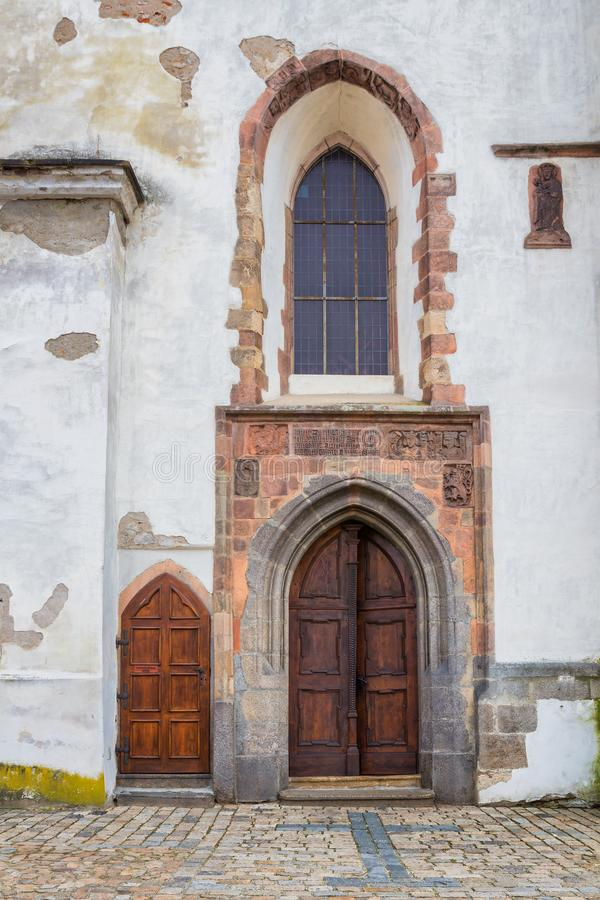 Vecchia porta di legno e finestra decorata della chiesa gotica fotografia stock
