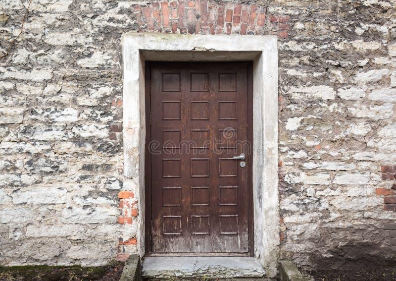 Vecchia porta di legno marrone in parete di pietra tallinn fotografie stock