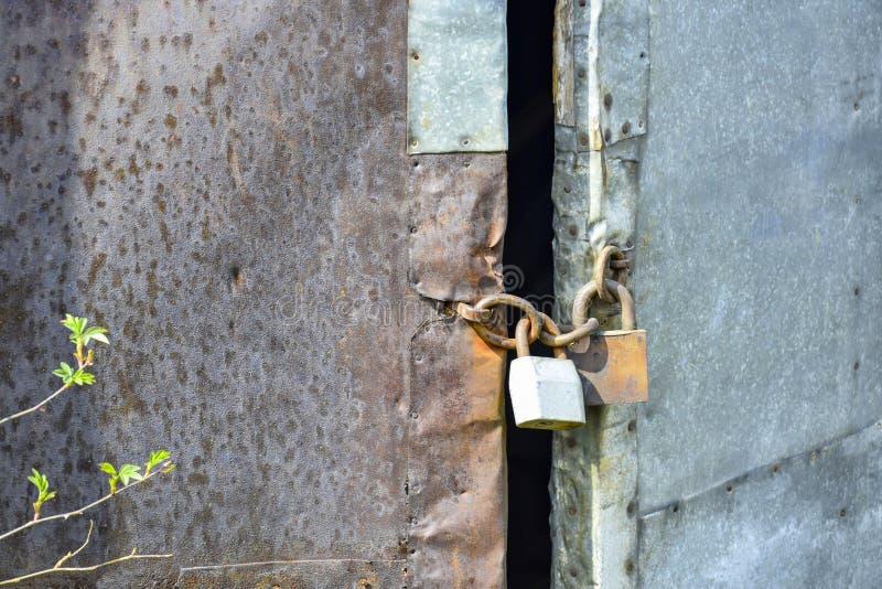 Vecchia porta di legno ricoperta con lo strato arrugginito del ferro ed il lamiera galvanizzato fotografia stock libera da diritti
