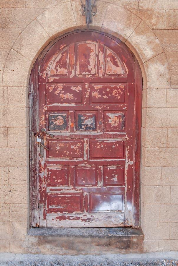 Vecchia porta di legno rosso scuro chiusa arrugginita su cemento giallo strutturato fotografia stock