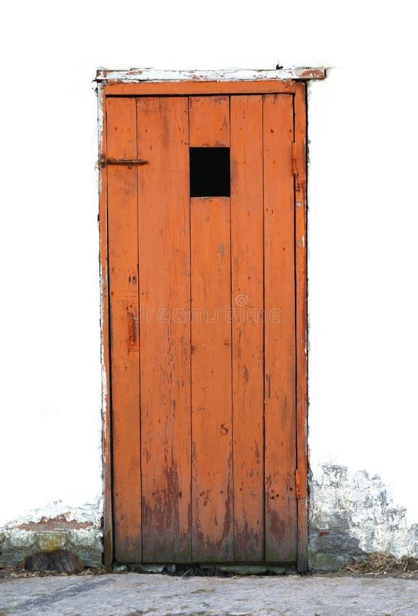 Vecchia porta di legno stagionata in una parete bianca fotografie stock
