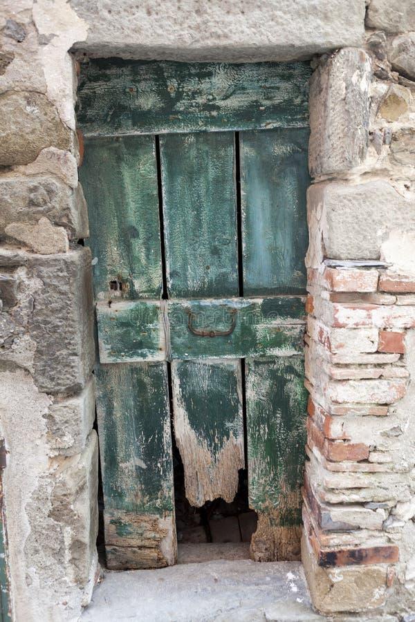 Vecchia porta di legno stracciata in una parete di pietra Polizia del lago italy Entrata ad una casa nel villaggio fotografie stock